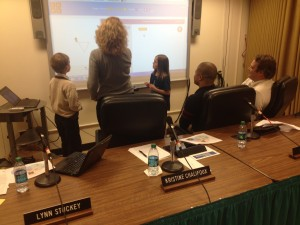 3 board members and 2 students work on a project at a SMART board