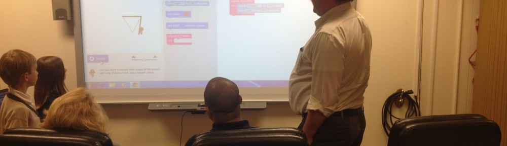 3 board members and 2 students contemplate how to complete a coding challenge at a whiteboard